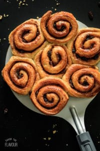 Cinnamon buns on a large metal spatula with a black background