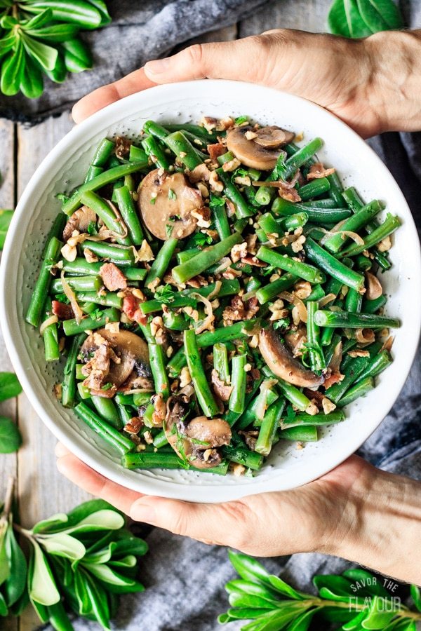 holding a bowl of green beans with bacon and mushrooms