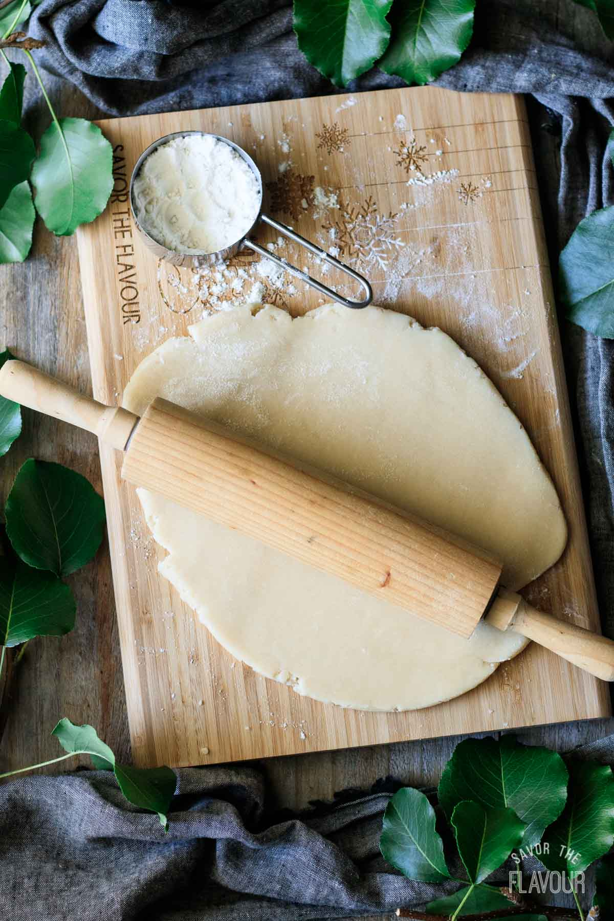 rolling out pastry on a wooden cutting board