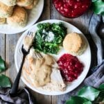 plate of turkey with giblet gravy, cranberry sauce, kale, and a biscuit
