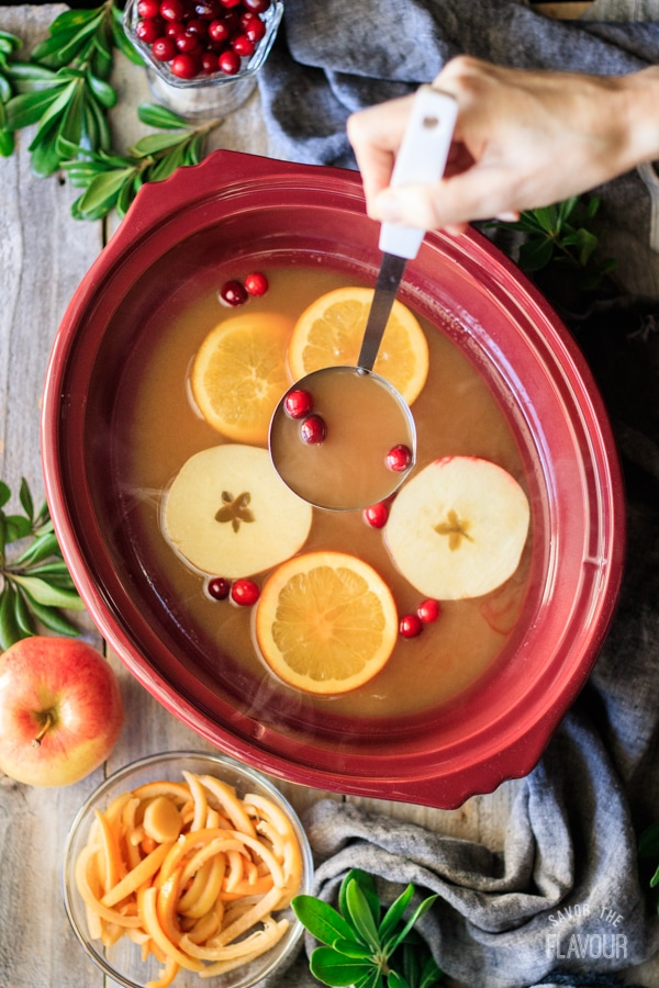 holding a ladle full of wassail