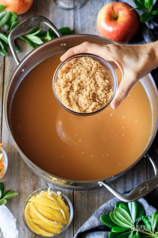 adding brown sugar to the pot of wassail
