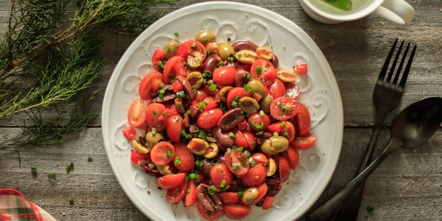 tomato olive salad on a white plate