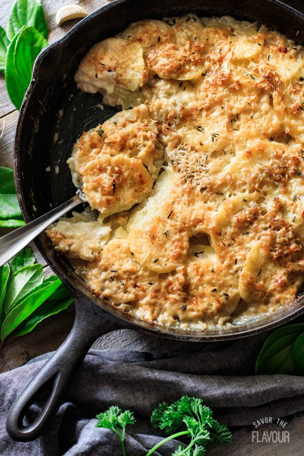 digging a spoon into a skillet of scalloped potatoes