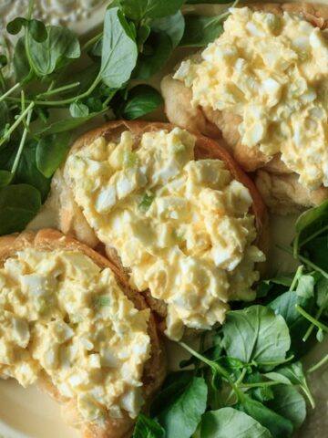 plate of egg salad on croissants