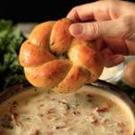 dipping garlic asiago knot into zuppa toscana