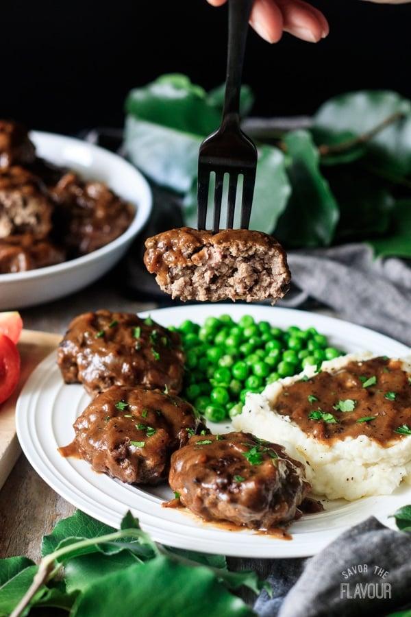 holding a piece of Salisbury steak on a fork
