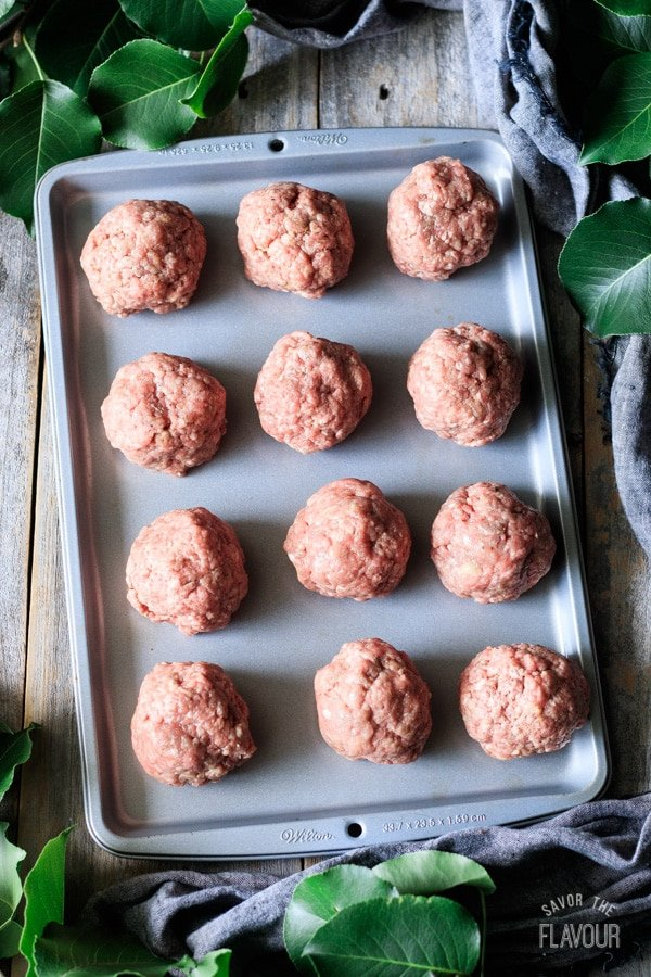 large balls of raw beef on a cookie sheet