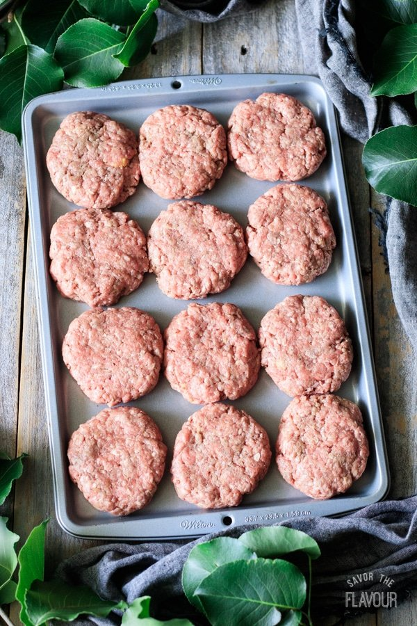 raw beef patties on a cookie sheet