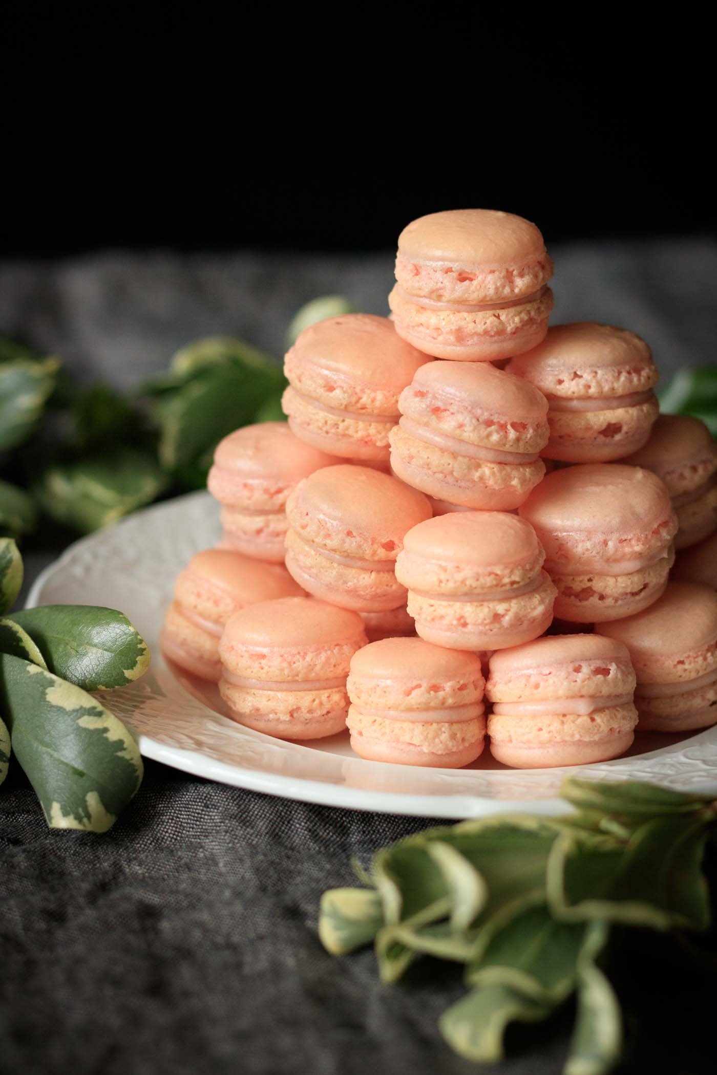 tower of mini strawberry macarons on a white plate