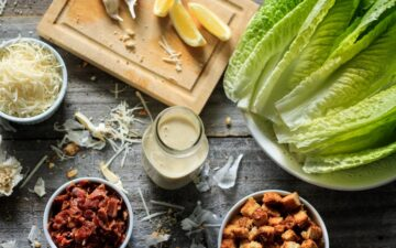bottle of Caesar salad dressing with lettuce, bacon, and croutons