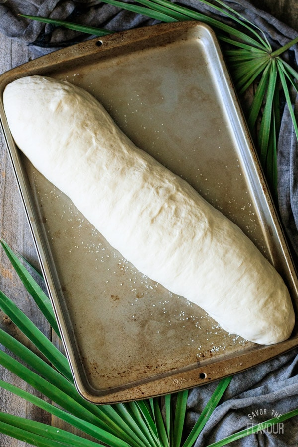 proved loaf of Cuban bread on a cookie sheet