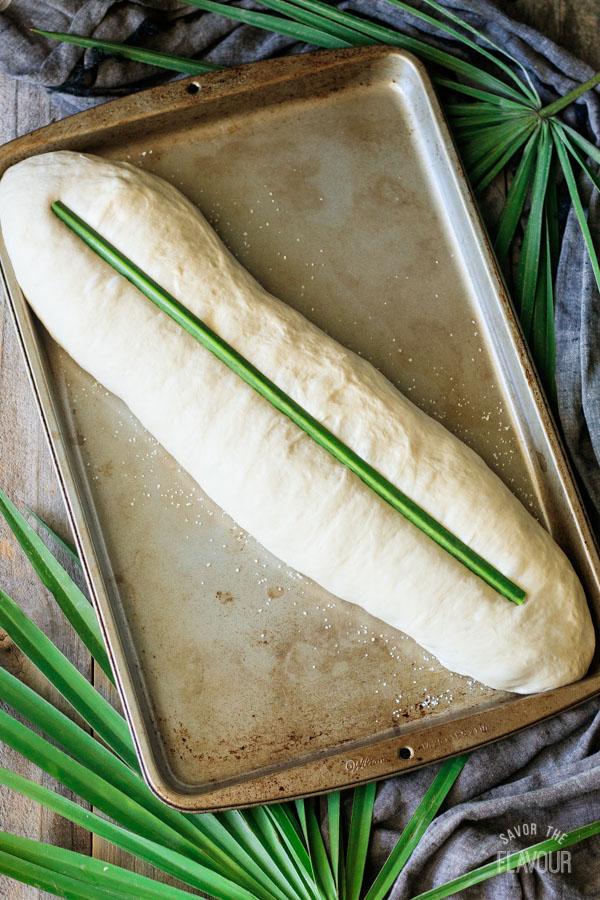 pressing palmetto stem into loaf of Cuban bread