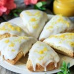 white plate of glazed lemon scones with lemon curd and pink flowers