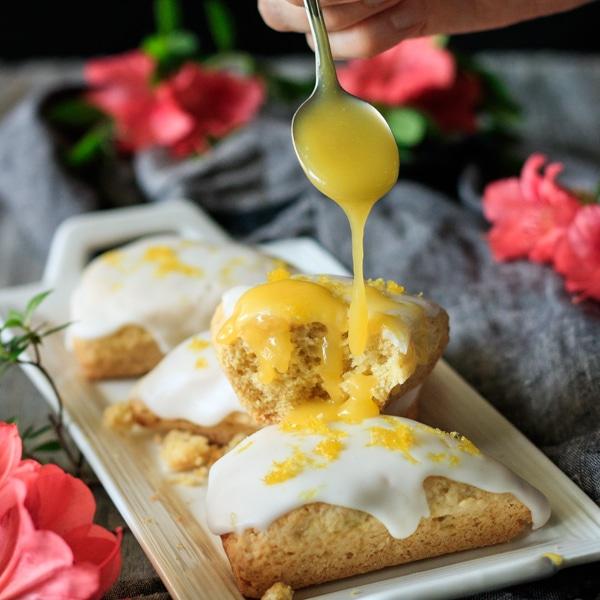 drizzling lemon curd on one of the lemon scones