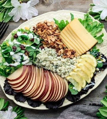salad on a yellow platter with two forks and salad dressing