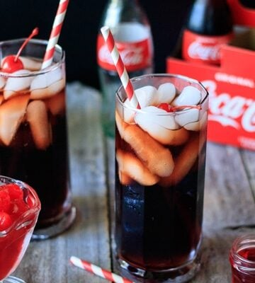 two Roy Rogers drinks with a glass dish of cherries