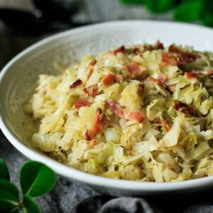 white bowl of fried cabbage with bacon and greenery