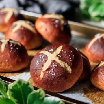 German pretzel buns on a cookie sheet with greenery