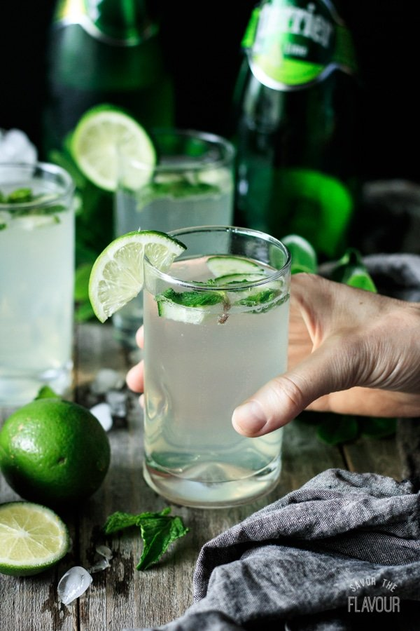 person holding a glass of lime and mint refresher with a lime slice on the rim of the glass