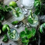 three glasses of lime and mint refresher with crushed ice and greenery