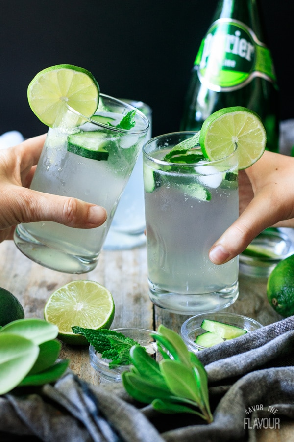 people doing a toast with two glasses of lime and mint refresher
