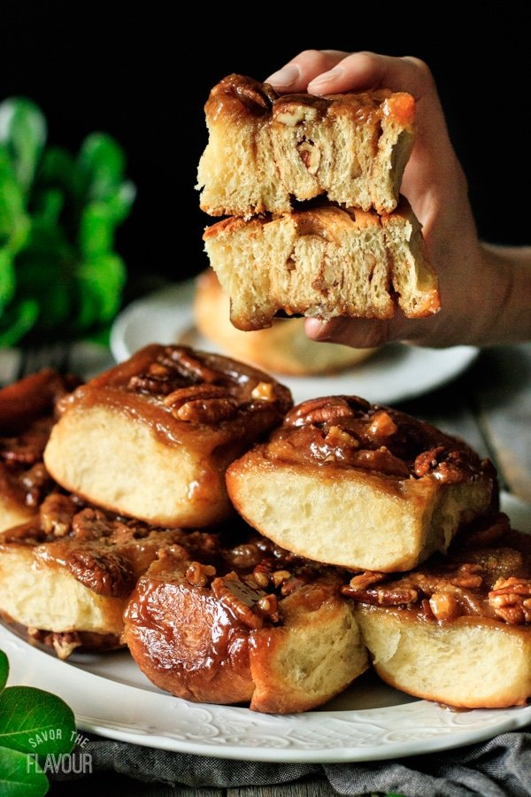 person holding a maple pecan sticky bun sliced in half