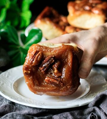 person holding a maple pecan sticky bun over a white plate