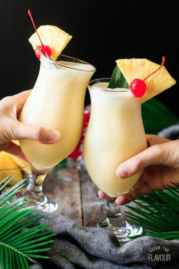people doing a toast with two glasses of piña colada