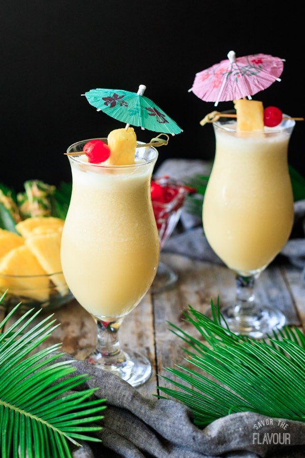 two glasses of piña colada with umbrellas