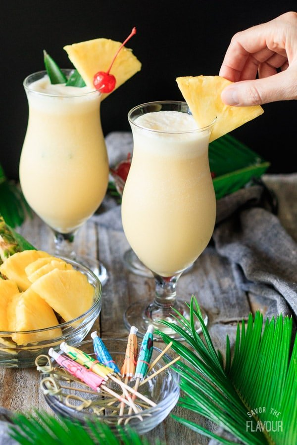 garnishing a piña colada with a pineapple slice