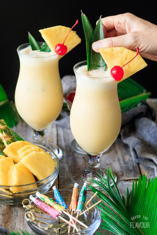 garnishing a piña colada with pineapple spikes