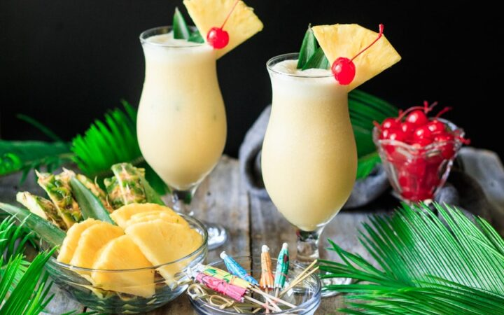 two glasses of piña colada with garnishes