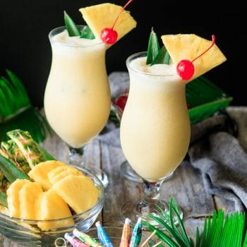 two glasses of piña colada with a bowl of pineapple