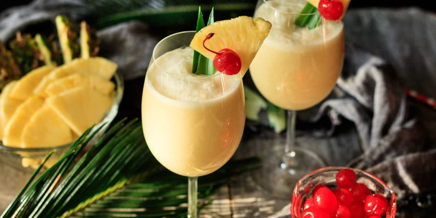 two glasses of piña colada with fresh pineapple and maraschino cherries