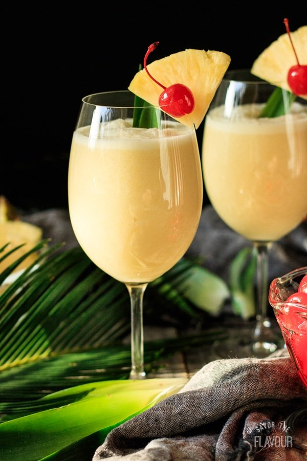 two glasses of piña colada with palm branches and maraschino cherries