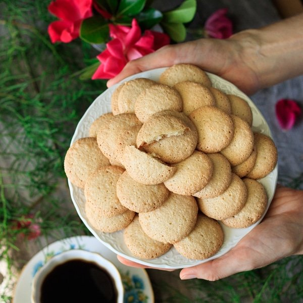 person holding a plate of gluten free ratafia biscuits with a cup of coffee and vase of roses in the background