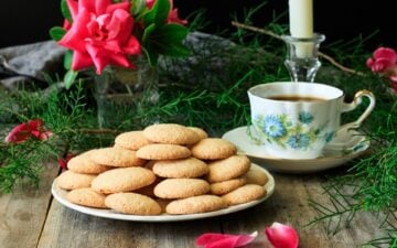 plate of gluten free ratafia biscuits with a vase of roses, coffee cup, and white candle in a glass holder