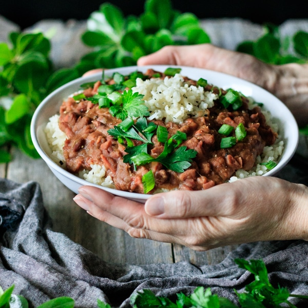 person holding a white bowl of red beans and rice