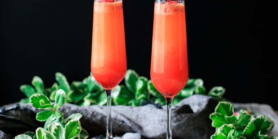 two strawberry citrus blush drinks with greenery and gray fabric