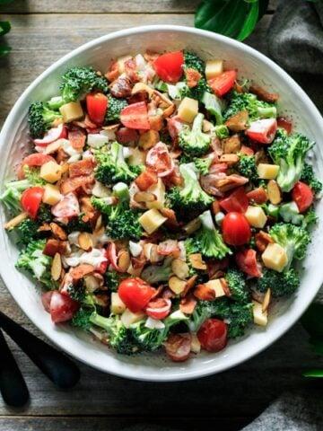 bowl of broccoli salad with greenery