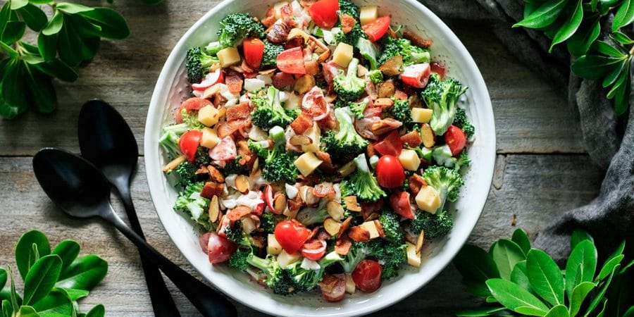 bowl of broccoli salad with greenery