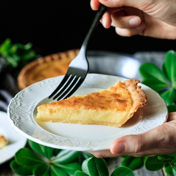 person holding a black fork and a slice of buttermilk pie on a white plate