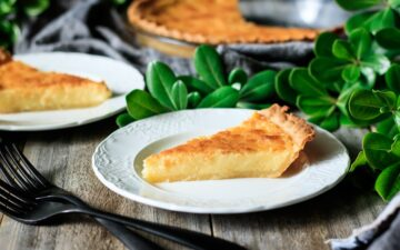 slice of buttermilk pie on a white plate with greenery