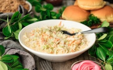 bowl of creamy coleslaw with pickled red onions, hamburger buns, pulled pork, and barbecue sauce