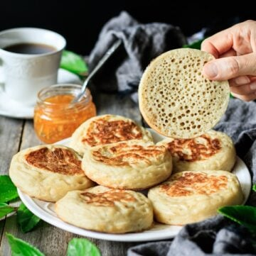 person holding an English crumpet sliced in half