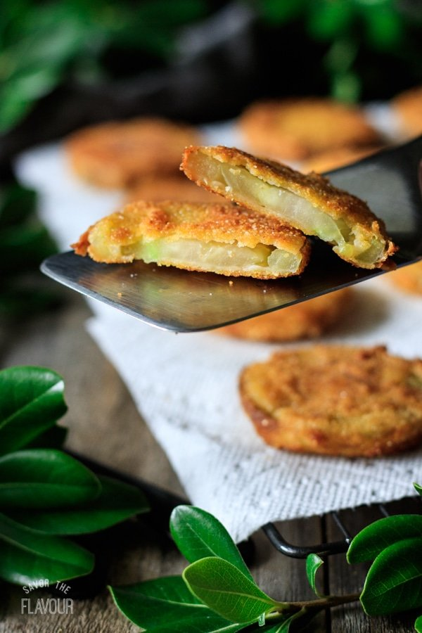 fried green tomato cut in half on a metal spatula