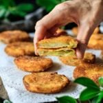 person holding a fried green tomato cut in half