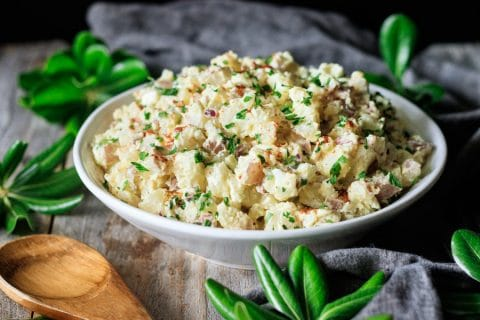 bowl of potato salad with a wooden spoon