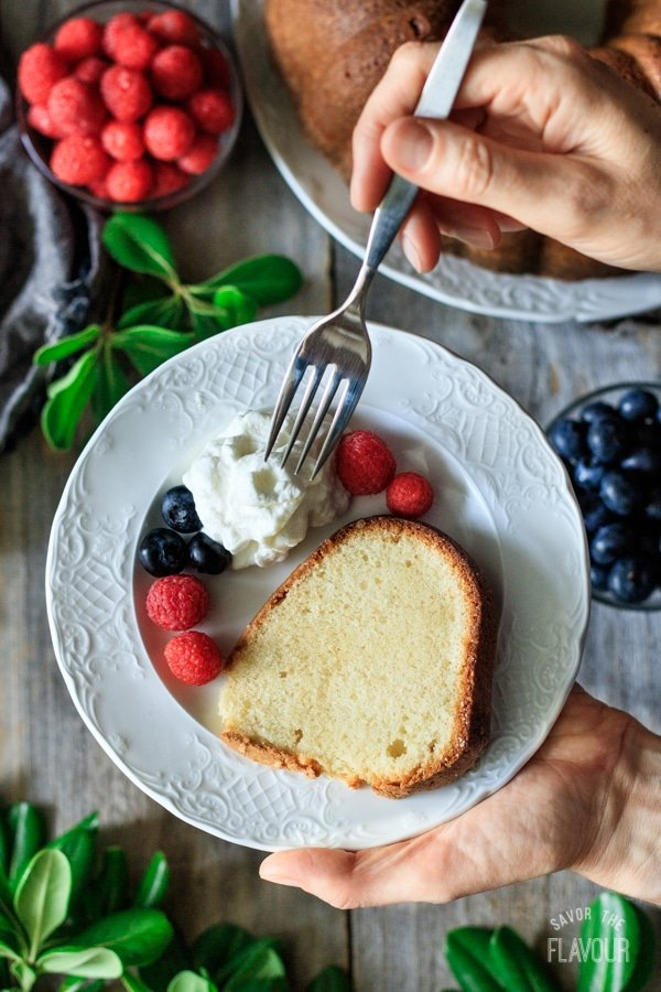 person holding a white plate of sour cream pound cake with fork